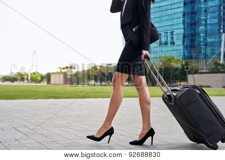 travel business woman pulling suitcase bag walking along sidewalk outdoors in modern urban city