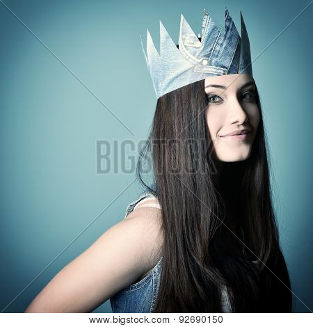 Pretty jeans princess. Beautiful girl in jeans and paper crown over blue background. Image toned