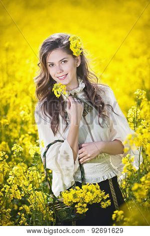 Young girl wearing elegant white blouse posing in canola field, outdoor shot