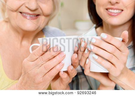 Grandmother and granddaughter with cups