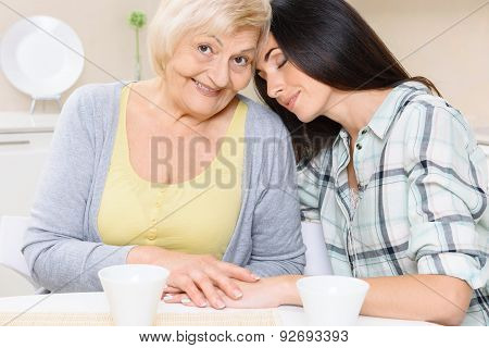 Grandmother and granddaughter sitting in kitchen