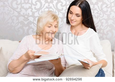 Grandmother with her daughter holding book