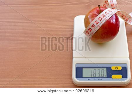 red apple with measure tape on electronic scale, diet concept