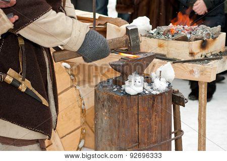 blacksmith at work with hot iron