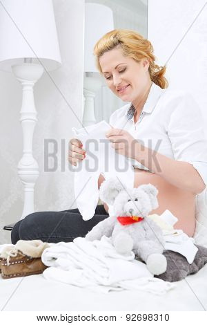Smiling woman sitting with baby clothes