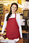 stock photo of cashiers  - Female Cashier At Supermarket Checkout - JPG
