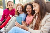 foto of 11 year old  - Young Girls Using Digital Tablets And Mobile Phones In Park - JPG