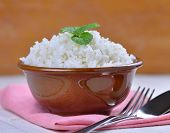 foto of ceramic bowl  - Cooked white rice garnished with mint in a ceramic bowl - JPG
