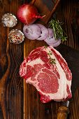 stock photo of ribeye steak  - raw beef Ribeye  steak   on wooden  table with vintage butcher cleaver knife and spices - JPG