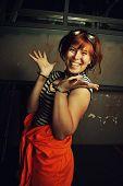 stock photo of lockups  - Funny redhead prisoner in orange clothes in her cell - JPG