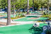 pic of miniature golf  - Greens on a miniature golf course under palm trees in the tropics - JPG