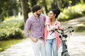 stock photo of tandem bicycle  - Young couple with a bicycle in a park - JPG