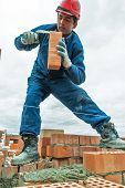 picture of bricklayer  - Tyumen, Russia - May 23, 2008: Construction of 18 floor brick residental house at intersection of streets of Gercena and Chelyuskincev. Bricklayer behind work ** Note: Visible grain at 100%, best at smaller sizes - JPG