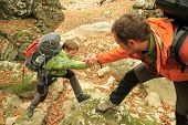 image of cliffs  - Man giving helping hand to friend to climb mountain rock cliff - JPG