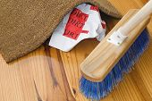 stock photo of smut  - A broom sweeps dirt under a rug in an attempt to conceal the truth - JPG