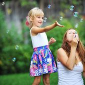 pic of blowers  - little girl and her mother play with bubble blower on green lawn