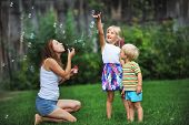 picture of blowers  - mother and her children play with bubble blower on green lawn
