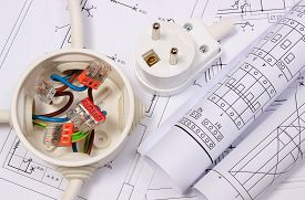 stock photo of electrical engineering  - Copper wire connections in electrical box rolls of electrical diagrams and electric plug on construction drawing of house accessories for engineering work energy concept - JPG