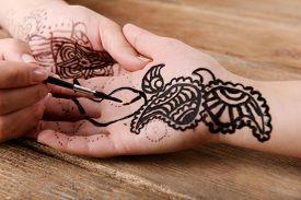 stock photo of mehndi  - Process of applying Mehndi on female hand close up - JPG