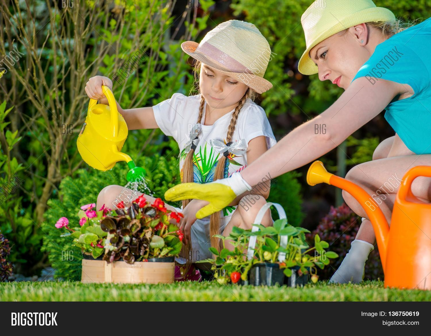 Mother And Daughter Working In Backyard Garden. Girl Learning How To Take  Care Of Garden