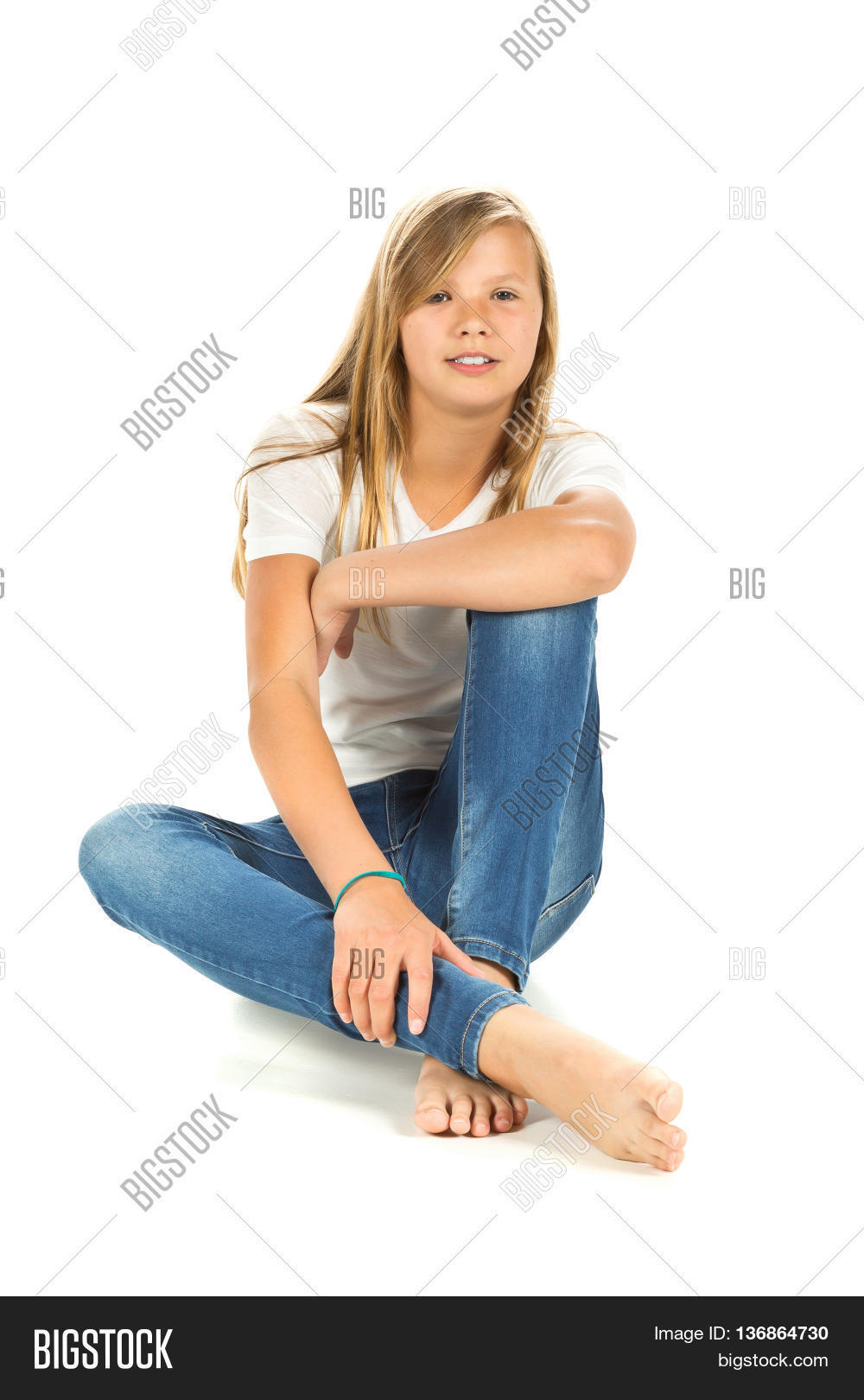 White t shirt and blue jeans - Young Girl Sitting Barefoot With White T Shirt And Blue Jeans Over White Background