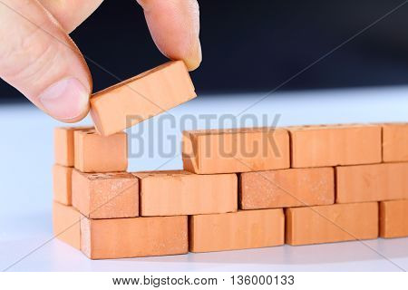 put in the last piece on a brick wall