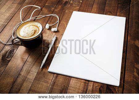 Blank branding template on vintage wooden table background. Blank letterhead coffee cup headphones and pen. Photo of blank stationery. Mock-up for your design. Responsive design template.