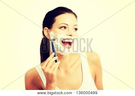 Beautiful young woman shaving her face
