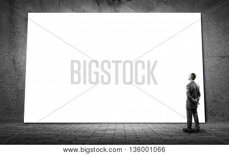 Rear view of businessman in concrete room looking at blank banner