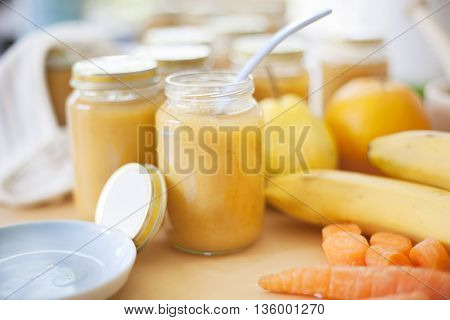 Homemade fresh baby food, surrounded by fruits