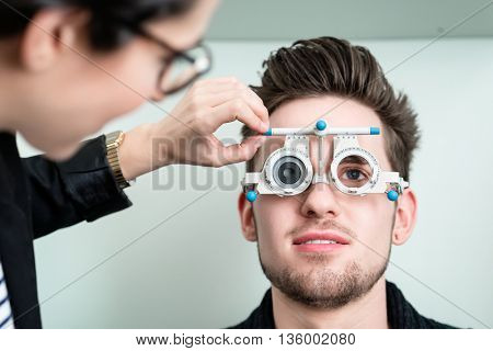 Man with optician at eyesight test for glasses