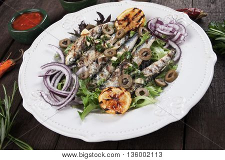 Grilled sardine fish with lettuce, olives, lemon and onion