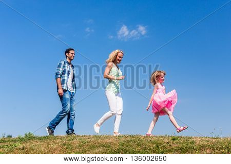 Family walks on meadow, Daughter leads, parents follow