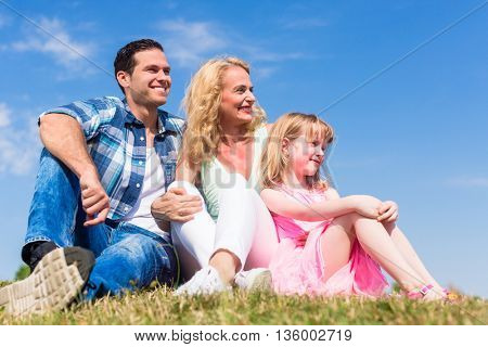 Dad, Mom and daughter sitting in meadow, asymmetric left, total view