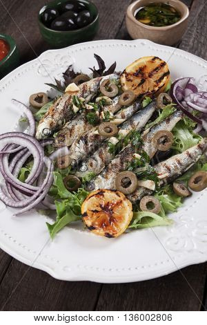 Grilled sardine fish served with lemon, olives, lettuce and onion