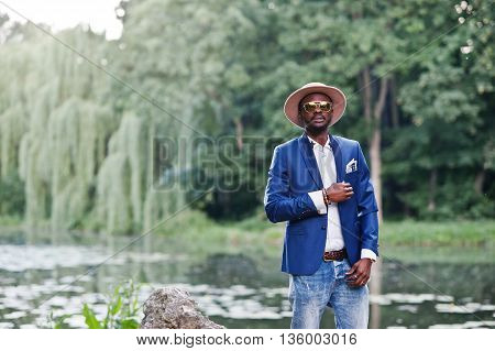 Portrait Of Stylish Rich Black Man At Blue Jacket, Hat And Sunglasses