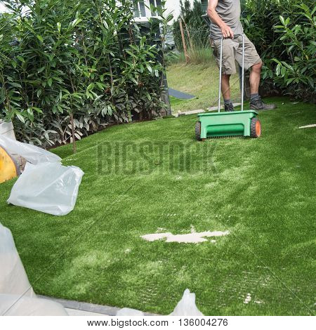 professional gardener puts sand on artificial turf