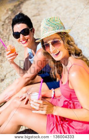 Women drinking cocktails at beach on swimming lake in sand