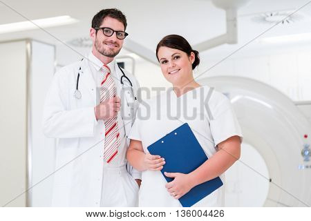 Doctor and nurse in front of CT scan machine in diagnostics room of hospital