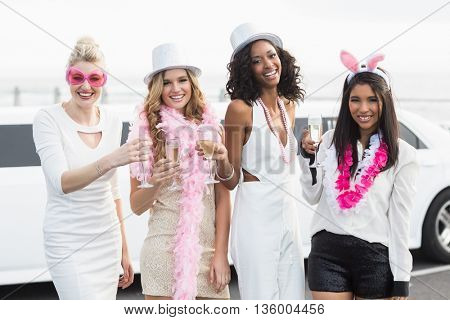 Frivolous women drinking champagne next to a limousine on a night out