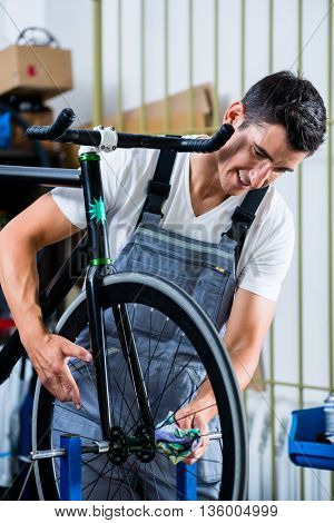 Mechanic repairing bicycle in his workshop