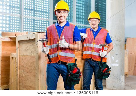 Two Asian Indonesian  construction worker on a tower building site close a wood box or cargo container with hammer and nail