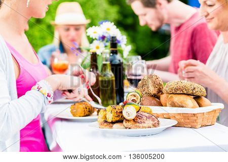 Friends eating bbq sausage and meat at garden or grill party