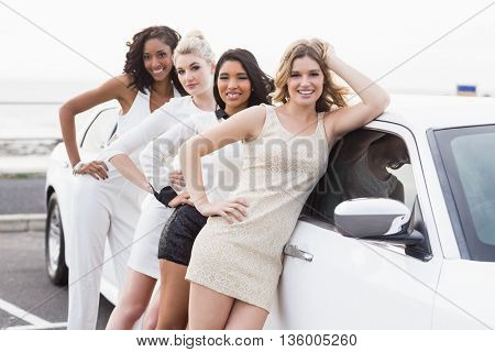 Well dressed women posing leaning on a limousine on a night out