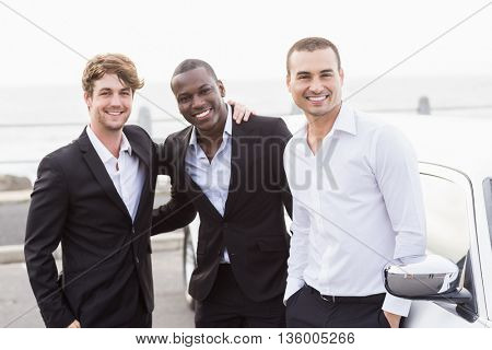 Well dressed men posing next to a limousine on a night out