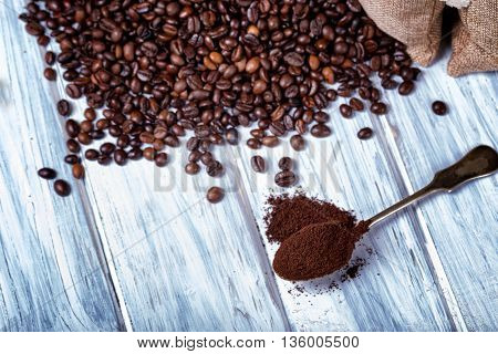 Ground coffee in spoon with coffee beans on a wooden table.