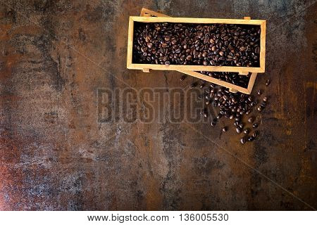 Wooden containers filled with cofee beans on the rust background. Low light.