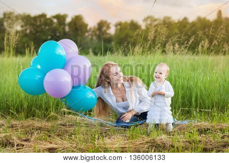 Young mother and her daughter sitting on the grass. Mum holds balloons