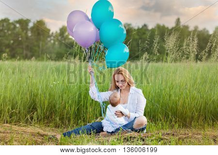 Mom sits on the grass with a child. Mom with balloons