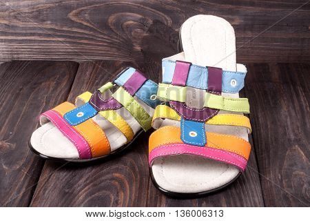 colorful female low-heeled sandals on dark wooden background.